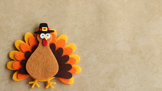 Felt turkey laying flat on a tan background with copy space 1166664684