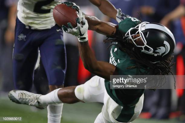 Felton Davis III of the Michigan State Spartans catches a fourth quarter pass in front of Ja'Marcus Ingram of the Utah State Aggies at Spartan...