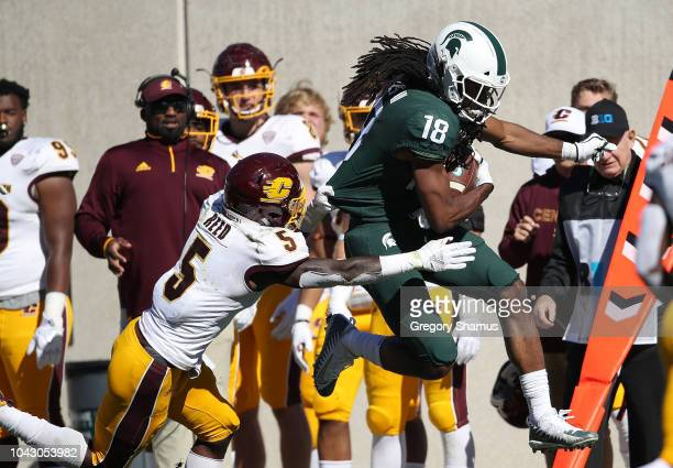 Felton Davis III of the Michigan State Spartans tries to escape the tackle of Devonni Reed of the Central Michigan Chippewas during the second half...