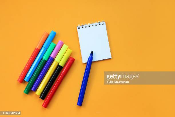 felt-tip pens and blank notepad on yellow background. concept of the educational process, study at school. back to school concept. - the_writer's_block stock pictures, royalty-free photos & images