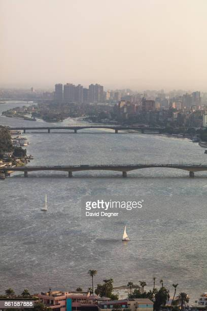 Feluccas and boats cross the the Nile and the bridges at sunset on September 24 2017 in Cairo Egypt Overview photos of Cairo's buildings cityscape...