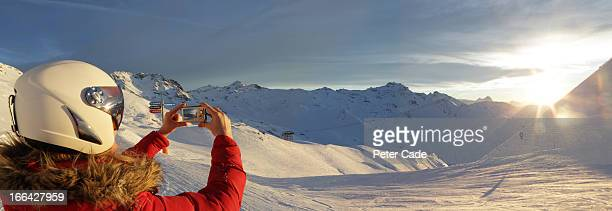 Femail skier taking photo of view