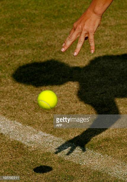 A femail tennis player prepares to serve during a tennis match on the third day of the Wimbledon Tennis Championships at the All England Lawn Tennis...