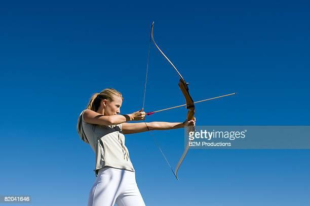Femal archer aiming arrow