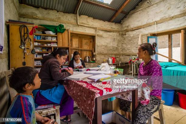 Femal doctor is practising in the medical station of the village, two patients waiting for treatment.
