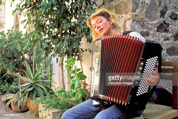 Female Accordion Player Sitting Outside Playing The Accordion