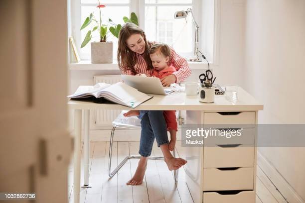 Female accountant sitting with daughter while working on laptop at home