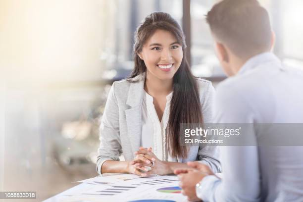 Female accountant smiles at her colleague during financial meeting
