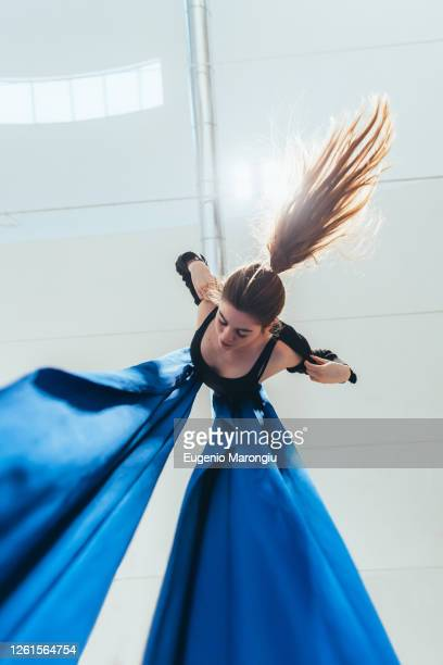 female acrobat aerialist practicing, suspended from a length of blue silk. - 空中曲芸師 ストックフォトと画像