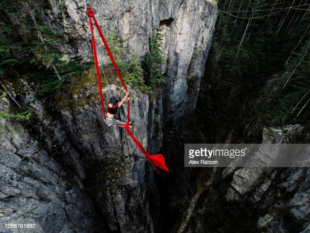 a female acrobatic performs on a red aerial silk that is suspended from a high-line spanning a tall rock gully face - insurrection stock pictures, royalty-free photos & images