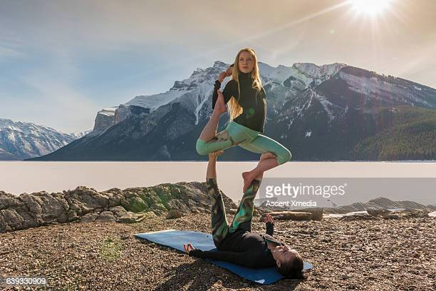 Female acrobats perform gymnastic duet, mountains