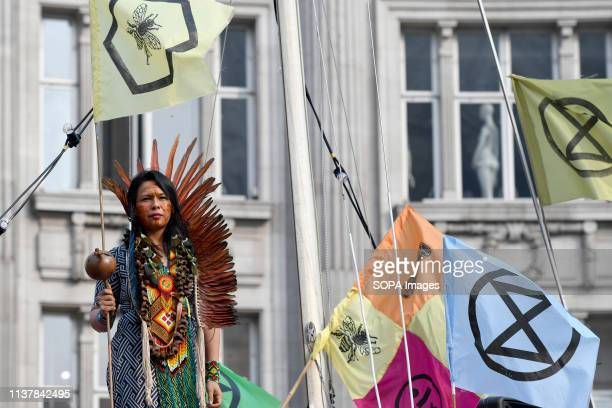 A female activist is seen holding a flag during the Extinction Rebellion Strike in London Environmental activists from Extinction Rebellion movement...