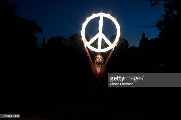 Female activist lifting shining peace symbol