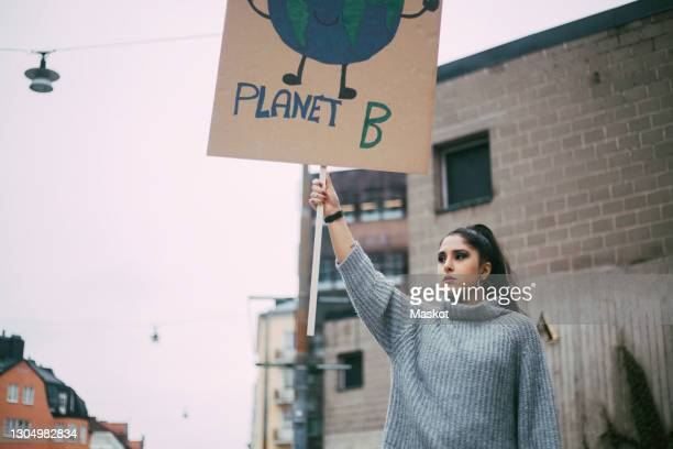 female activist looking away while holding planet earth poster during social movement - social justice concept stock pictures, royalty-free photos & images
