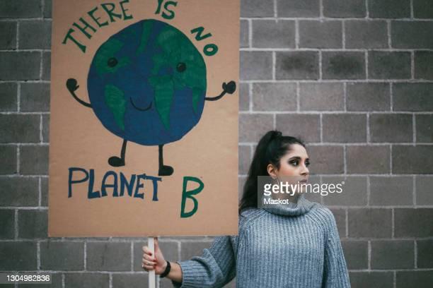 female activist looking away while holding planet earth poster against wall - politiek en staatsbestuur stockfoto's en -beelden