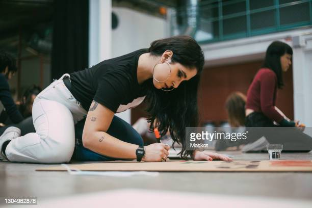 female activist preparing signboard while sitting in building to protest against social issues - revolution stock pictures, royalty-free photos & images