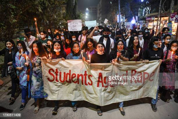Female activists and students hold a banner, placards and lit candles during the demonstration. Female activists and classmates take part in a...