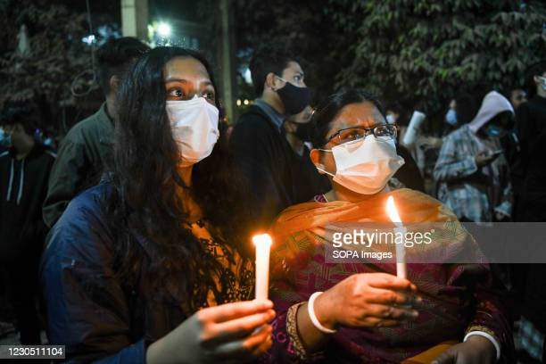 Female activists wearing face masks hold lit candles during the demonstration. Female activists and classmates take part in a candlelight protest...