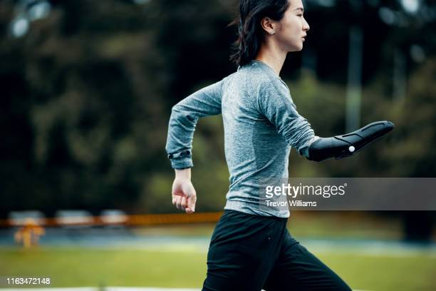 female adaptive athlete training at a running track - amputee woman stock pictures, royalty-free photos & images
