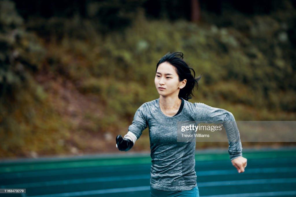 Female adaptive athlete training at a running track : ストックフォト