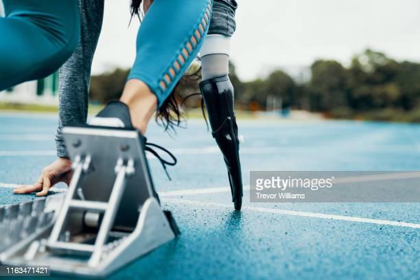 female adaptive athlete training for competition at a university athletics stadium - 四肢切断 ストックフォトと画像