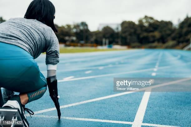 Female adaptive athlete training for competition at a university athletics stadium