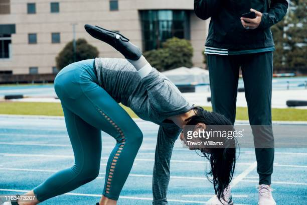 female adaptive athlete training with her coach at an athletics track - coach stock pictures, royalty-free photos & images