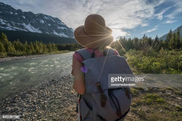mujer que admira la naturaleza por el río al atardecer - banff fotografías e imágenes de stock