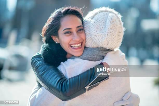 weibliche erwachsene glücklich, ihre schwester zu sehen - nordafrikanischer abstammung stock-fotos und bilder