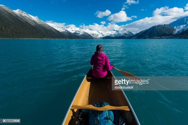 Female adventurer canoeing an alpine lake