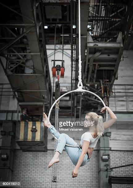 female aerial hoop artist in steel factory - 空中曲芸師 ストックフォトと画像