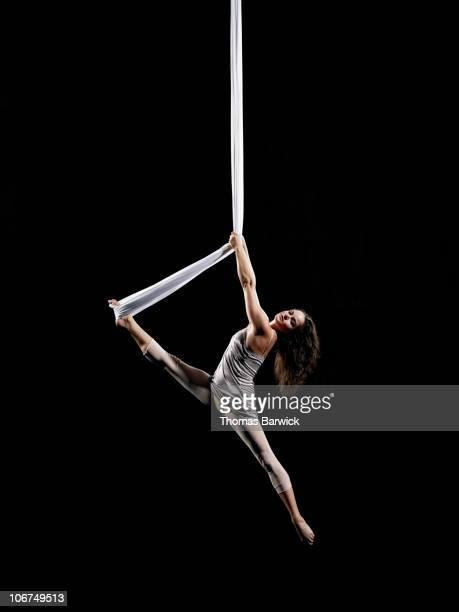 Female aerialist swinging on suspended silk