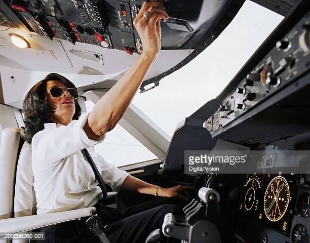 Female aeroplane pilot, operating controls, low angle view