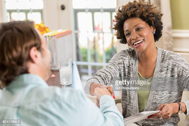 Female African American entrepreneur greets client in home office