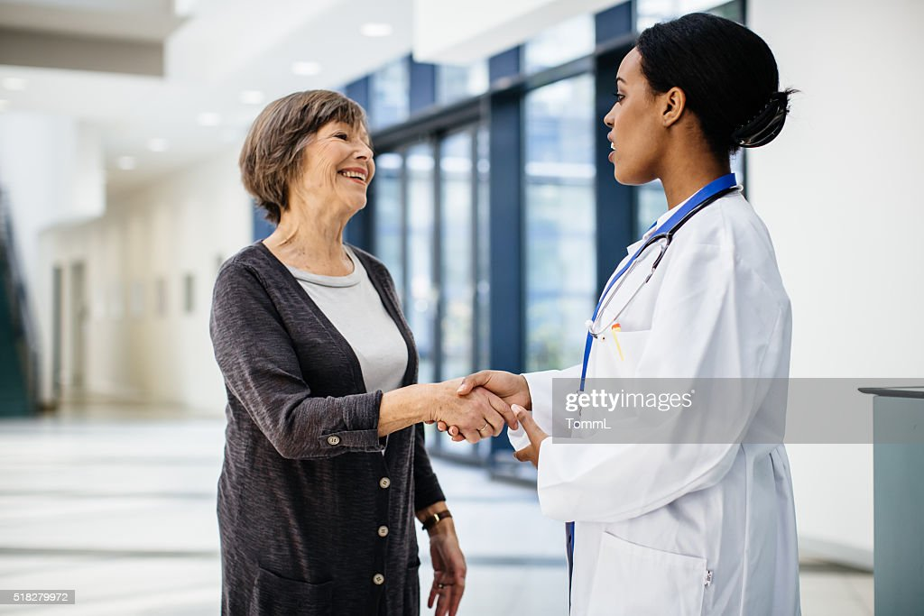 Female african doctor welcomes senior patient : Stock Photo