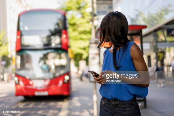 female afro-american using smartphone at bus stop in london, united kingdom - station stock pictures, royalty-free photos & images