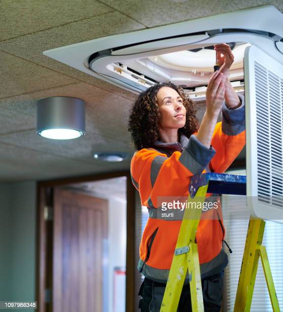 female air con maintenance engineer - hvac stock photos and pictures