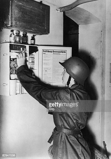 A female air raid warden checks the contents of a household first aid cupboard Germany circa 1938 Exact regulations specifying what it should contain...