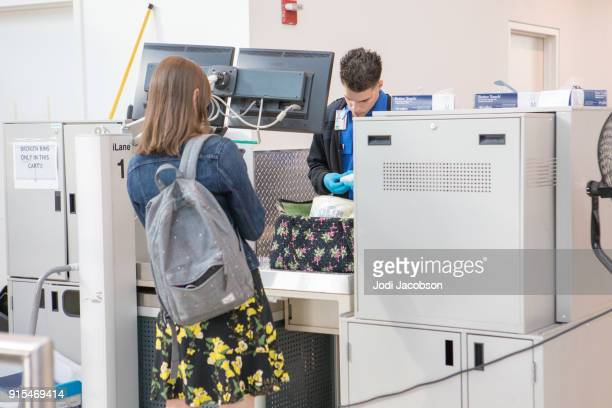 female airline passenger  having bag searched by tsa - transportation security administration stock pictures, royalty-free photos & images