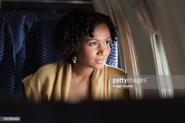 female airplane passenger looking out of window - commercial aircraft stock pictures, royalty-free photos & images
