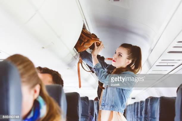 female airplane passenger storing handbag in locker - storage compartment stock pictures, royalty-free photos & images