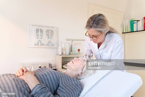female alternative practitioner giving senior woman injection acupuncture - older woman bending over stock pictures, royalty-free photos & images