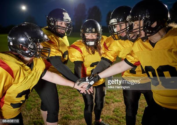 female american football team huddling and chanting - safety american football player stock pictures, royalty-free photos & images