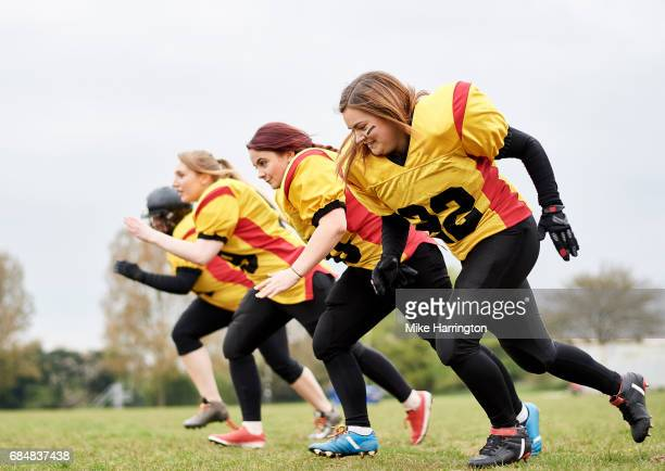 female american football team running together - safety american football player stock pictures, royalty-free photos & images