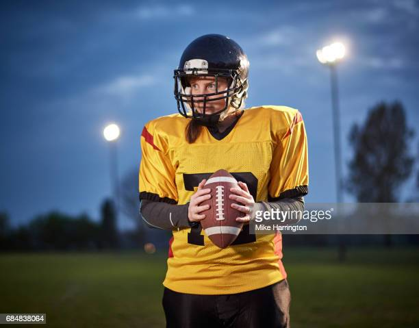 female american footballer holding ball with both hands - safety american football player stock pictures, royalty-free photos & images