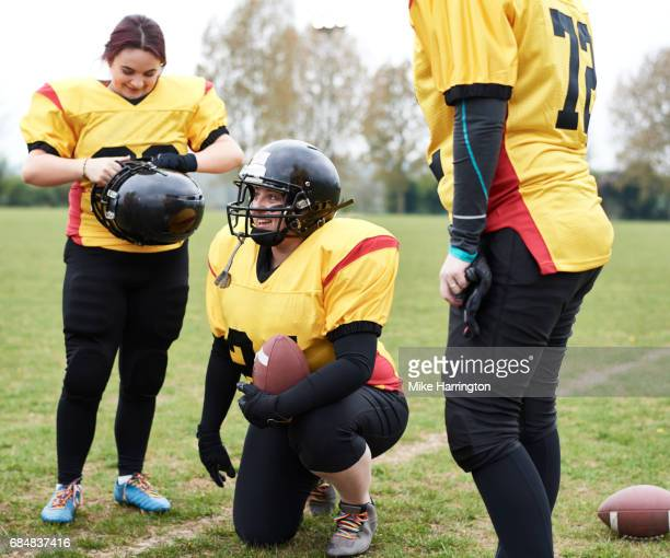 female american footballer laughing with teammates - safety american football player stock pictures, royalty-free photos & images