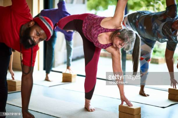 female amputee balancing in half moon pose using yoga block - limb body part stock pictures, royalty-free photos & images