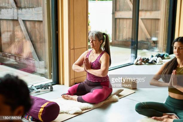 female amputee in prayer position in yoga studio - travel stock pictures, royalty-free photos & images