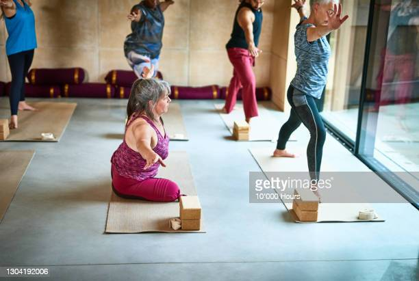 female amputee on yoga mat with arm out - disability stock pictures, royalty-free photos & images