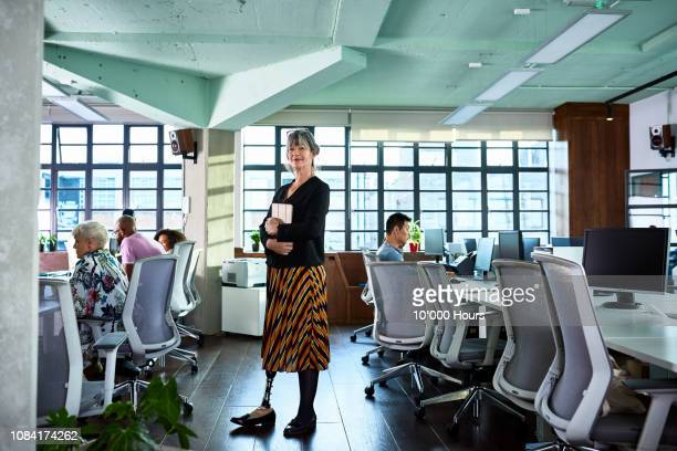 female amputee standing in office looking at camera and smiling - amputee woman stock pictures, royalty-free photos & images